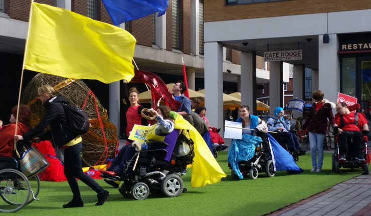 Group of people including adults with learning disabilities and physical disabilities in a parade with coloured flags, in Exeter city centre