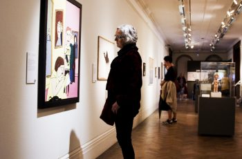 A person looking at a painting in the Alternative Visions Exhibition