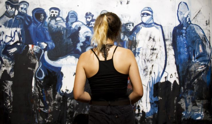 Photo of a person standing in front of a painting by Steve Burden