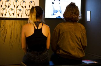 Two people sitting on a bench in the Alternative Visions exhibition, watching a video screen