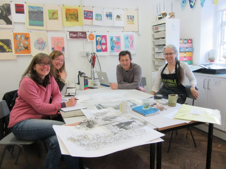 People at Double Elephant Print workshop sit around a table