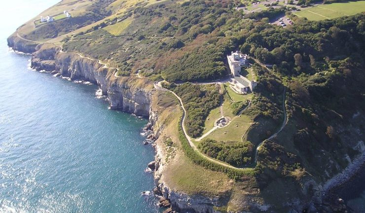 Photo of Durlston Country Park - a grassy cliff with a building on the coast.