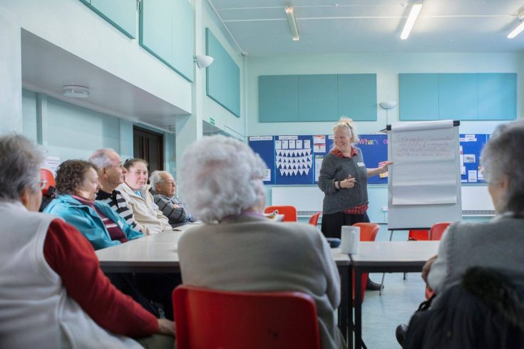 Poet Stands in front of a room of older people, doing a workshop
