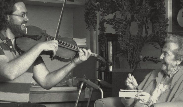 A black and white photo of a violinist playing music to an elderly hospital patient