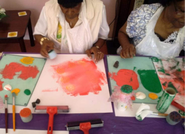 2 ladies sat at a table making art prints in a workshop