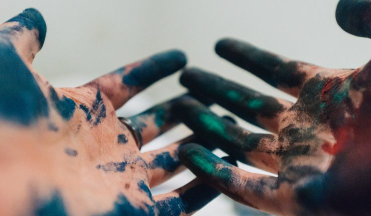 Hands with coloured paint on them