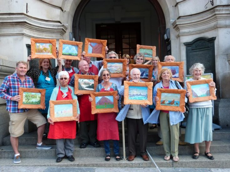 A group of people standing on the steps of Plymouth Museum and Art Gallery, holding up artwork they have made