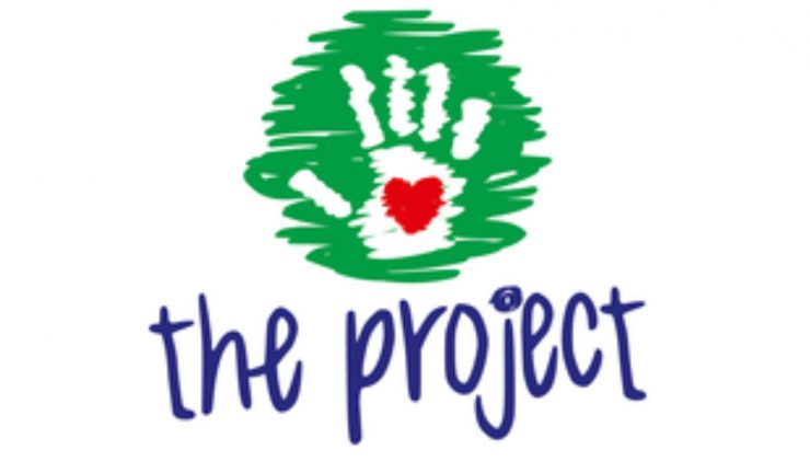 Logo for The Project with a hand containing a red heart on a green scribble background