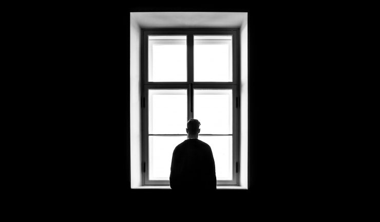 Black and white photo of an standing alone in front of window