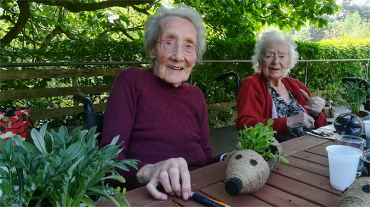 Two older ladies sitting at a table in a garden doing creative activities with plants