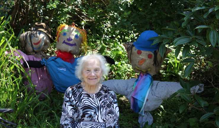 older lady standing in between leafy plants in a garden, with 3 scarecrows
