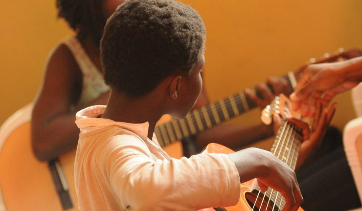 boy playing guitar in a music lesson