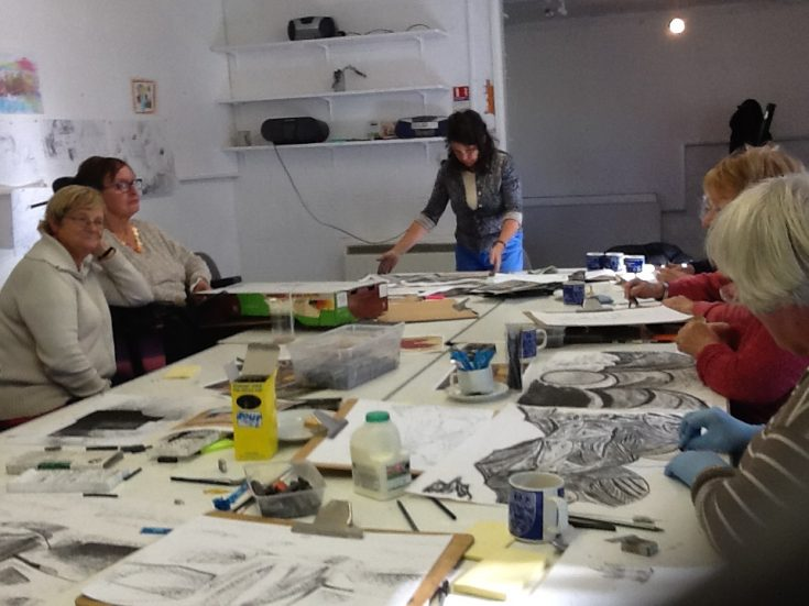 People sitting around a table doing an art workshop