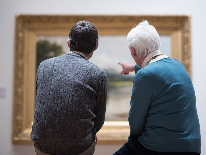 A museum attendant and an older man point at a painting in a museum and talk about it
