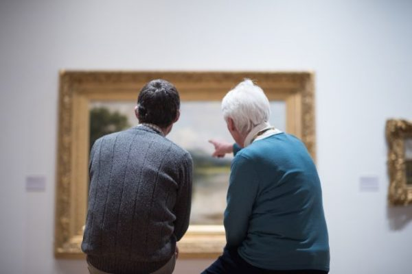 A young man and an old man in a museum discussing a painting