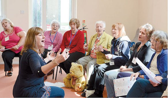 People with dementia sat in a group singing, with a singing workshop leader in front