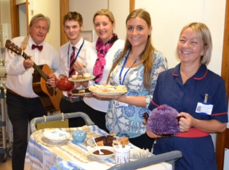 Hospital staff playing music and offering tea and cake from a trolley