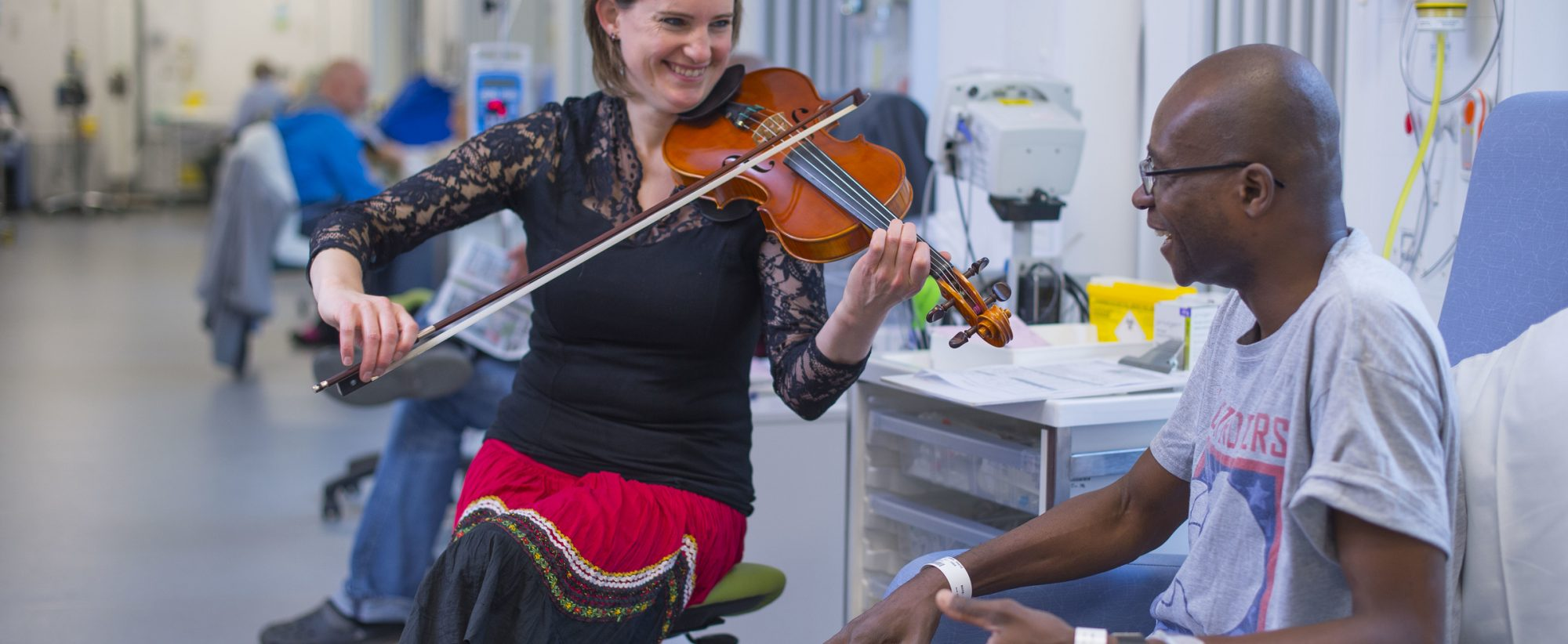 A female musician plays violin to a hospital patient