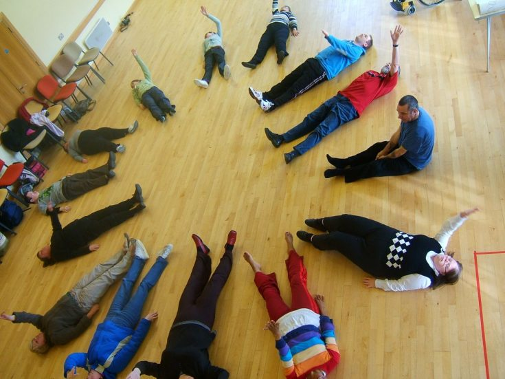 A group of people lie in a circle on a wooden floor, moving their arms