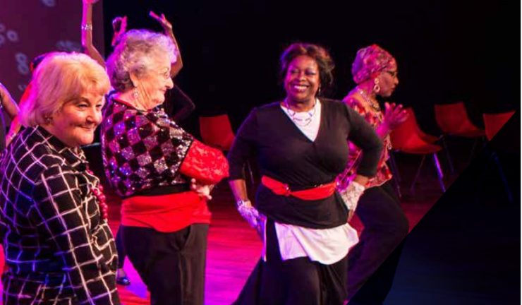 A group of ladies dancing on stage, under pink and red lighting