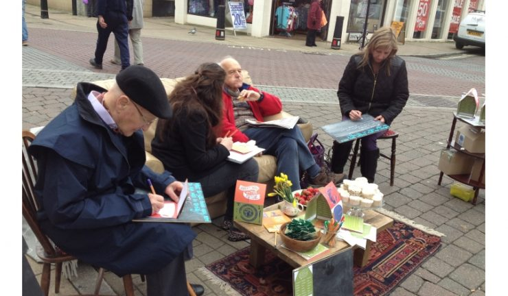 A group of older people and workshop facilitators sitting on tables and chairs outside, on a high street pavement, doing a creative activity