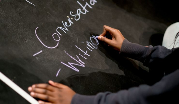 A person's hands writing on a chalk board