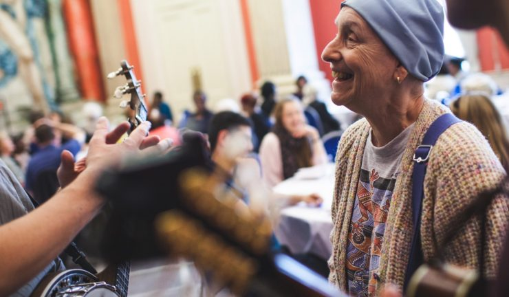 An older lady wearing a head scarf smiles while musicians nearby play music