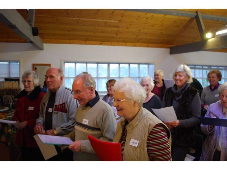 A group of older people singing together, holding sheets of lyrics