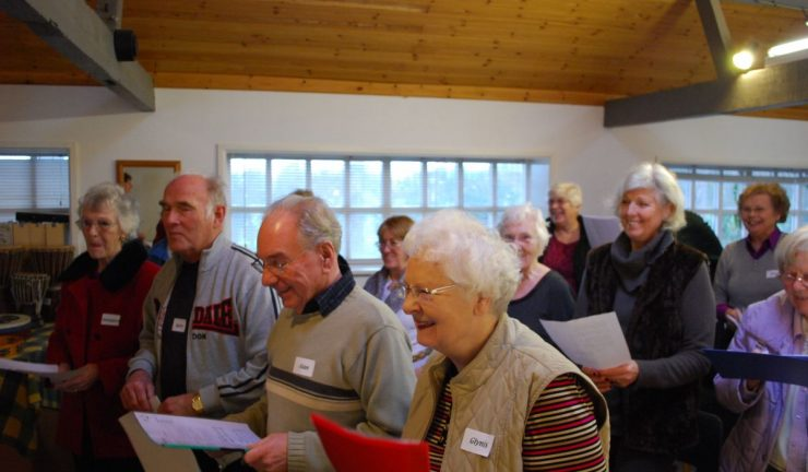 A group of older people singing together, holding sheets of lyrics
