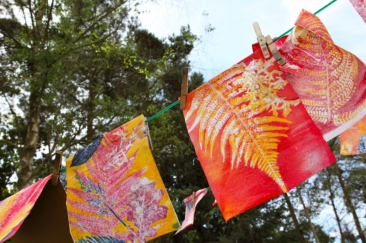 Fabric with red and yellow leaf prints hang up to dry on a washing line outside