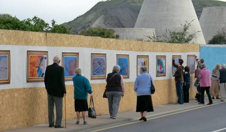 Students install artworks on wooden boards set up on a pavement buy a road in Ilfracombe