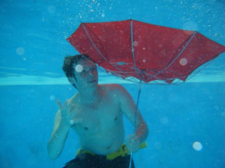 A man underwater with an inside-out umbrella