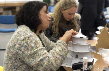 2 people build cardboard buildings in a creative workshop