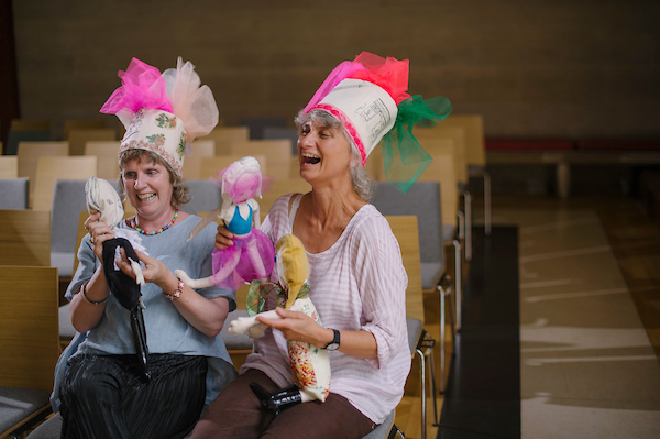 two ladies sitting in a conference hall, wearing colourful hats, laughing and using puppets