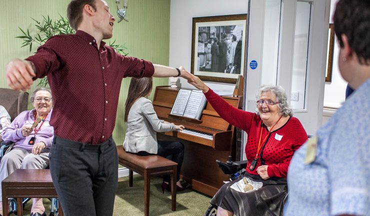 A man sings and dances with an older lady in a wheelchair, in a care home