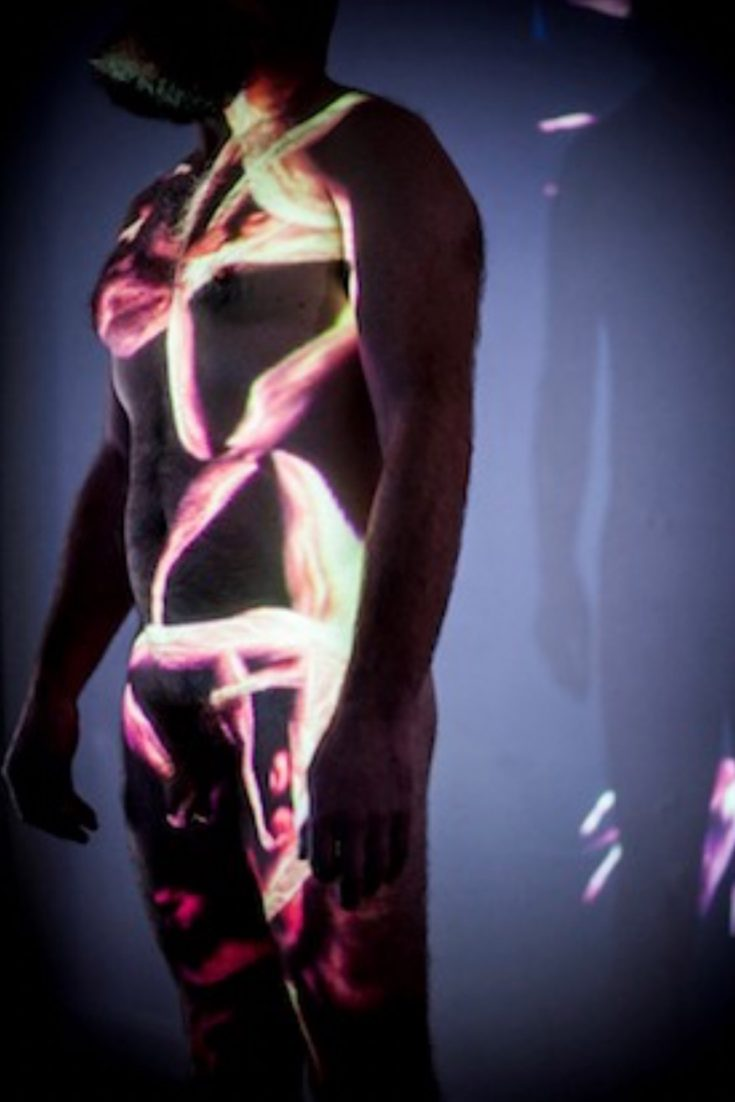 A naked man with graphic colourful shapes projected on his body in the dar
