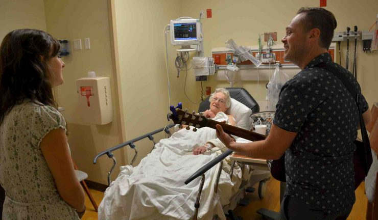 A musician and a staff member sing to a lady in a hospital bed
