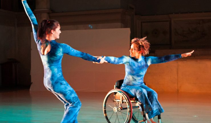 two dancers wearing mottled blue outfits, one in a wheelchair, link hands in a dance