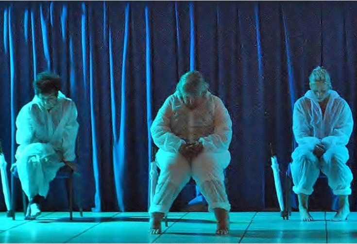 3 performers in white all-in-one costumes sitting on a stage on 3 chairs, with blue lighting