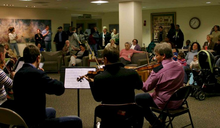 A group of violinists play music in a hospital waiting room