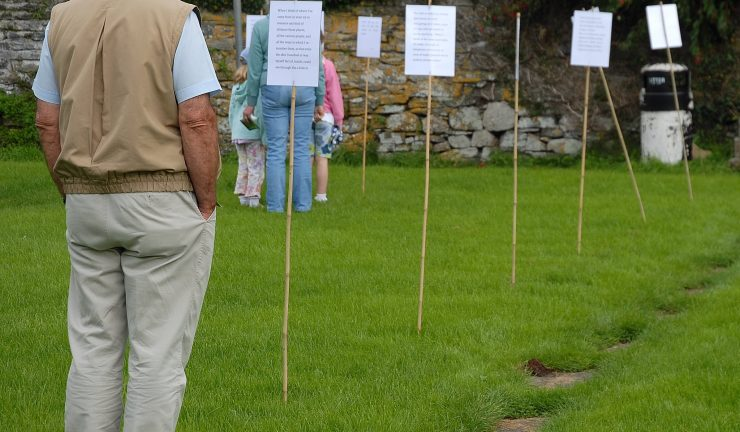 A couple of people stand in a garden reading signs on sticks