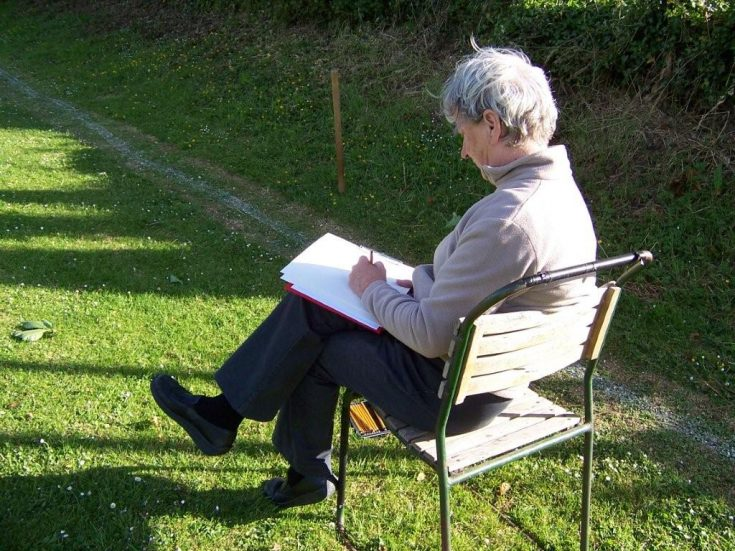 A person sits on a chair outside, drawing in a sketchbook