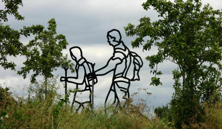 Cutout metal sculpture of two people walking, installed in between 2 trees