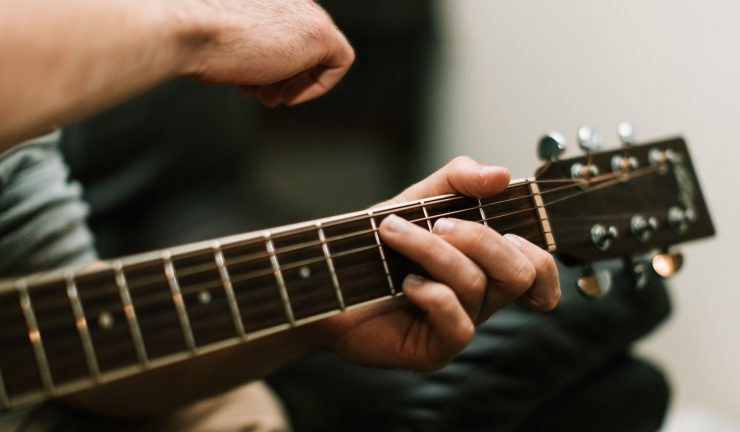 person playing guitar while sitting down