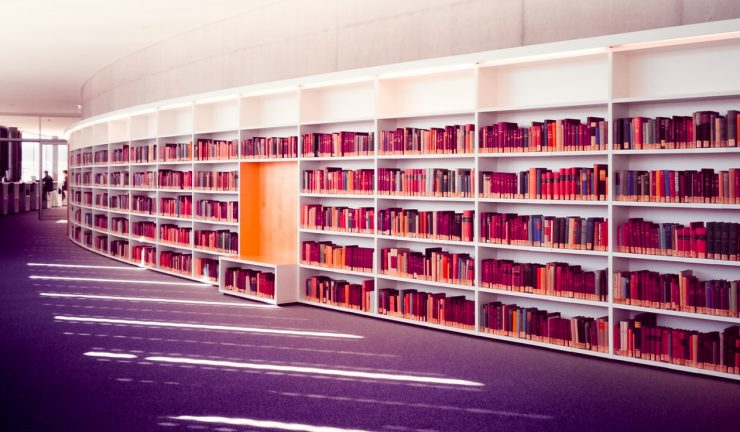 A library with books on white shelves and a purple carpet