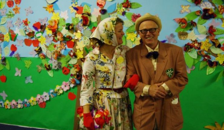 Two people in old fashioned clothes link arms against a bright floral background