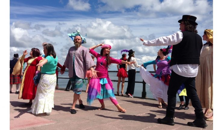 A group of people in brightly coloured clothes and hats dancing on the pavement by the seafront.