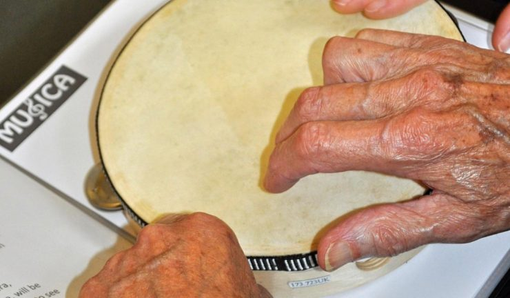 An older person's hands playing a tambourine