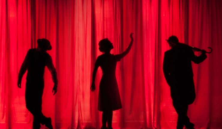 silhouettes of three actors against a red curtain