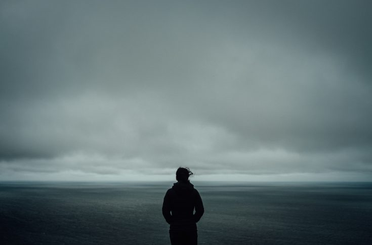 one person stands on a beach with a grey gloomy sky